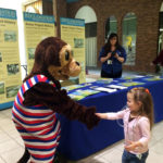Photo of a man in an otter costume shaking hands with a little girl