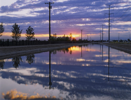 Photo of a purple sunset over a canal with clear, reflective water