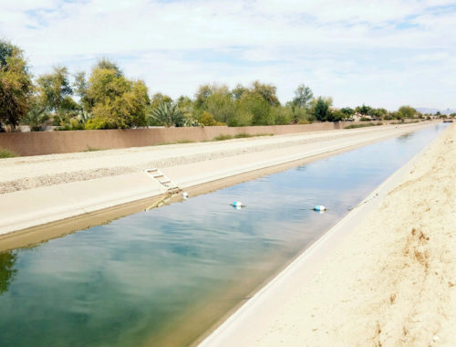 Photo of a canal with clear water in an arid landscape