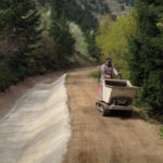 Photo of concrete buggy transporting concrete along a dirt road