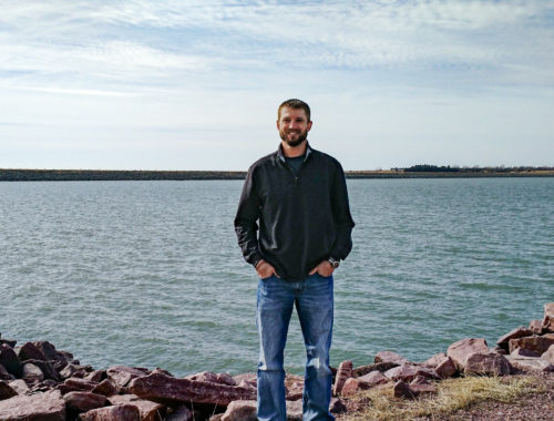Photo portrait of Matt Lukasiewicz standing in front of a lake