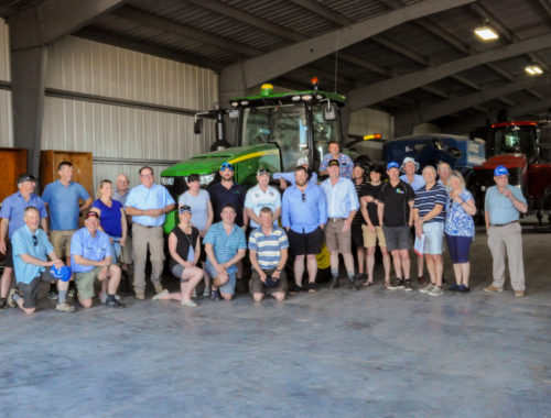 Group photo in warehouse in front of tractor