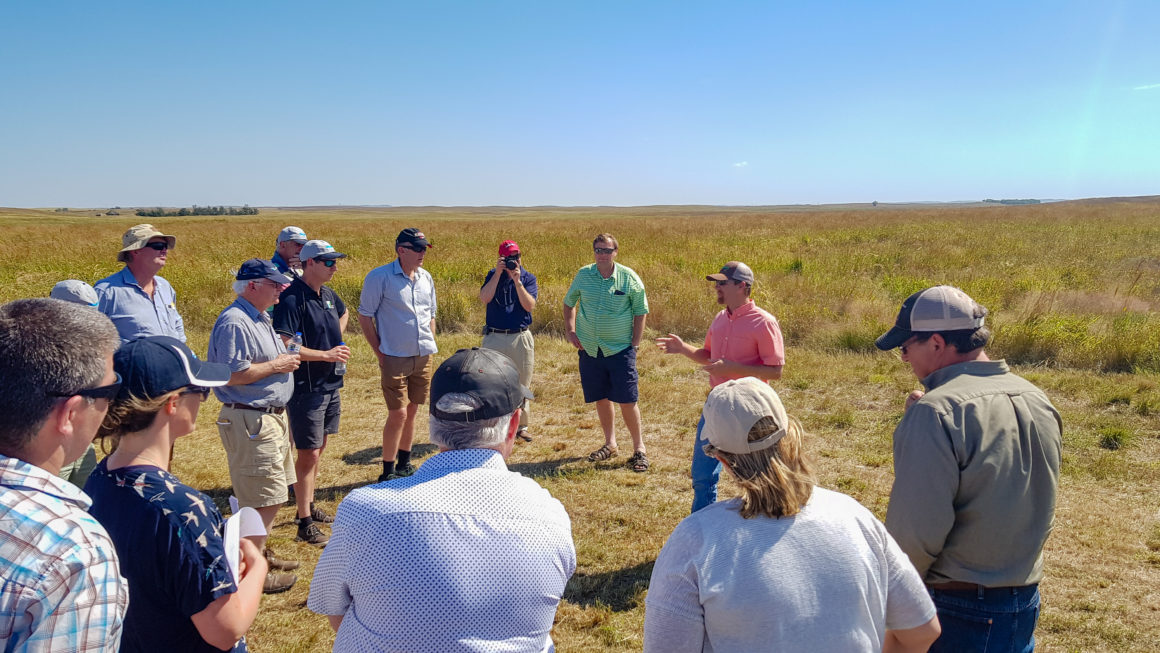 Photo of tour group standing in a loose circle on a field