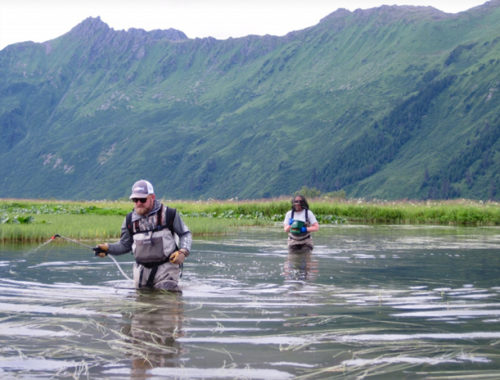 Photo of Dr. Andrew Skibo and Kate Mohatt wading through water and applying chemicals to the water. Mountains in the background.